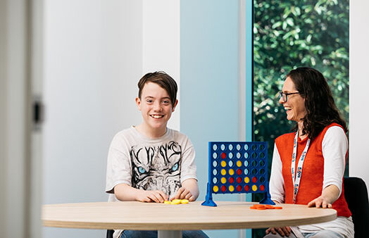 Boy and carer playing connect 4, Kudos