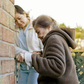 Carer helping elderly woman up a stair into a building