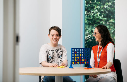 Kudos client and staff member playing Connect 4 game