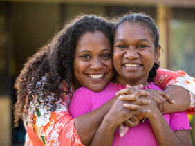 Two young Australian aboriginal female students outdoors with their arms around each other smiling at the camera.