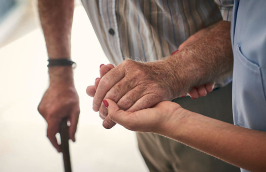 Close up of carer supporting patient by hand, aged care, istock