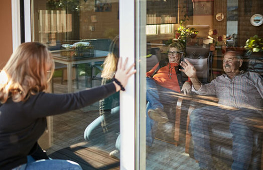Granddaughter visiting grandparents on their 70s, they are sitting on sofa indoors at home and granddaughter is outdoors talking to them in the other side of the window in times of COVID-19. istockphoto