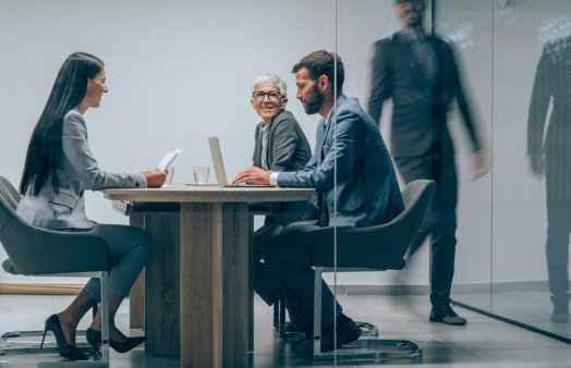 Shot of a group of business people having a meeting in board room. Businessman walking in blurred motion around his colleagues. Group of entrepreneurs on meeting in board room. Corporate business team on meeting in the office. The view is through glass.
